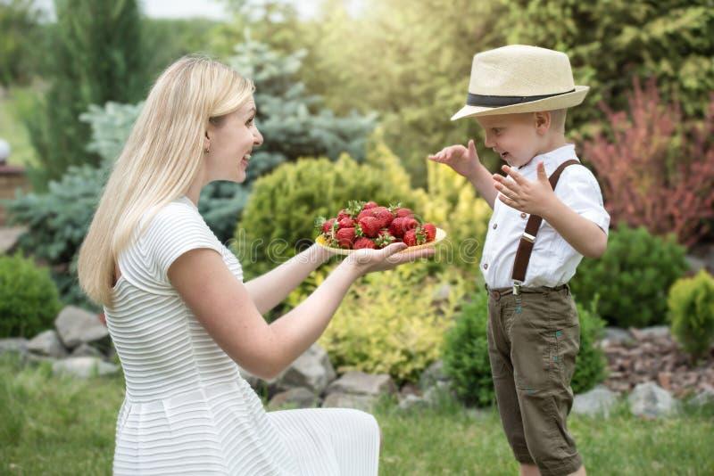 一个年轻母亲对待她的小儿子成熟芬芳草莓 免版税库存照片