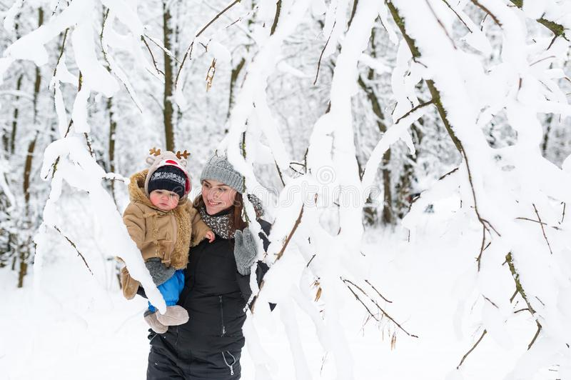 一个年轻母亲拿着她的她的胳膊的小儿子 步行在冬天森林里 免版税库存图片