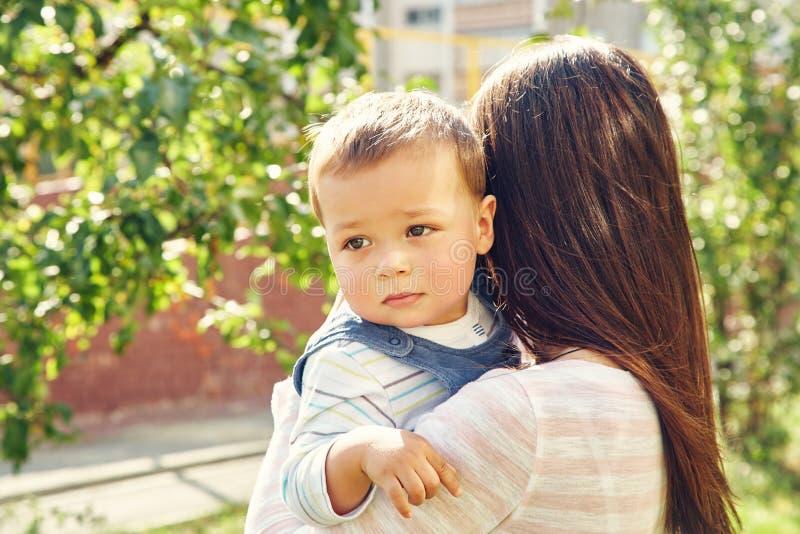 一个年轻母亲的画象有婴孩的 两个绿色牛仔裤妈妈儿子顶层佩带 免版税图库摄影