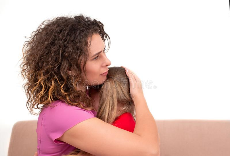一个年轻母亲镇定她的女儿 女孩哭泣,并且她的母亲拥抱她充满爱 免版税图库摄影