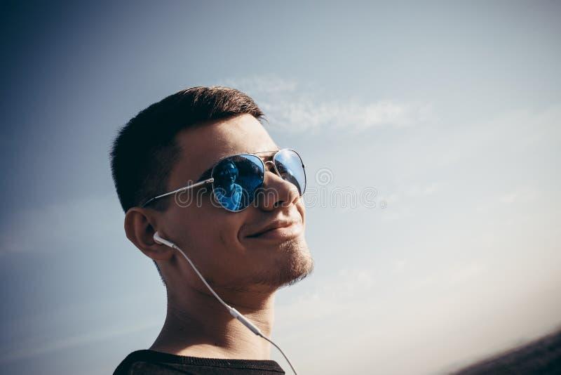 一个年轻爱恋的人的画象耳机和佩带的玻璃的 免版税库存图片