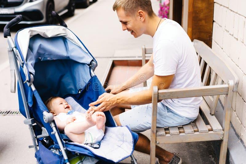 一个年轻父亲坐长凳在他新出生的儿子的婴儿推车旁边 库存图片