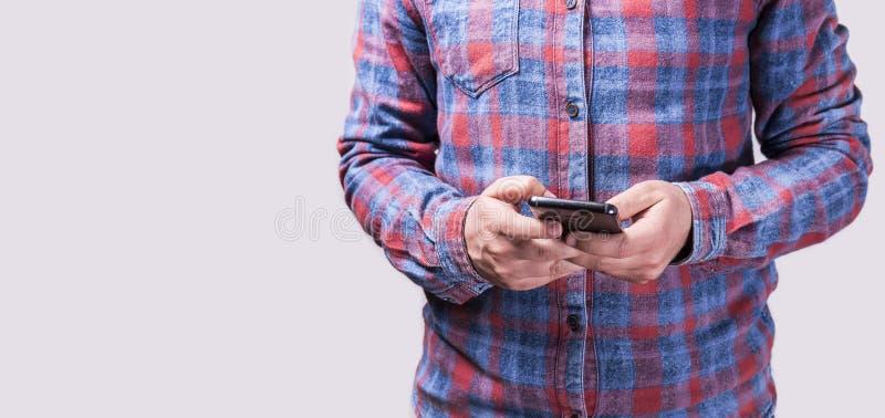 一个年轻男子穿着彩色衬衫拿着手机的特写 库存照片