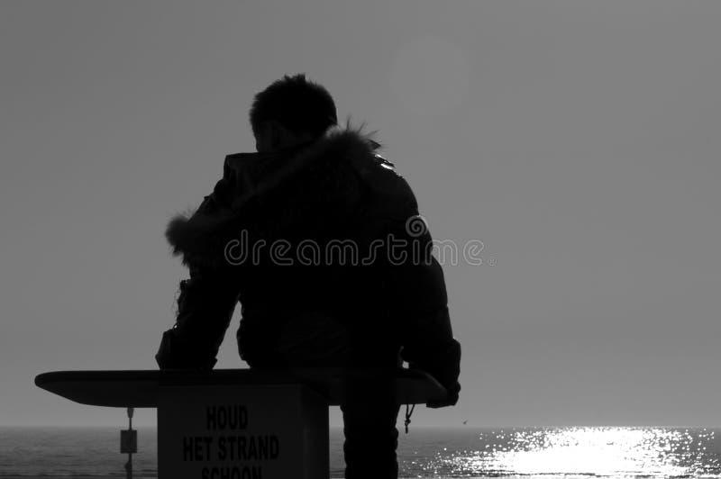 一个年轻男孩的剪影在海附近的 库存图片
