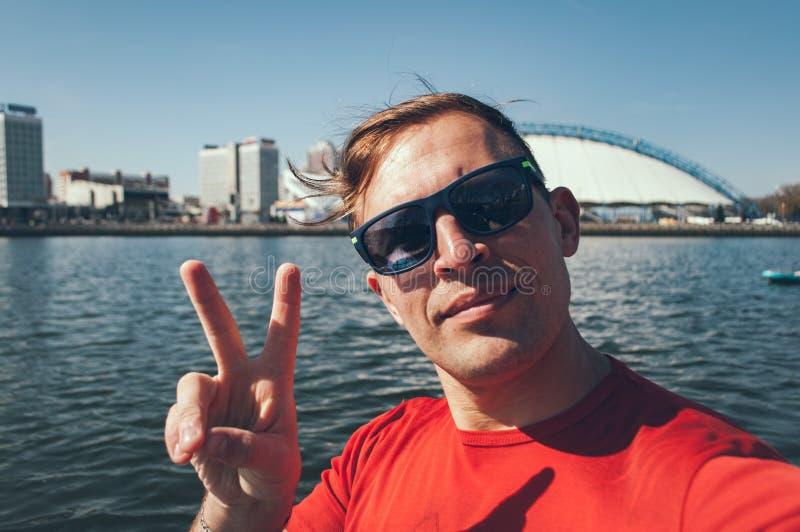 一个年轻男孩的露天Selfie在城市的背景的好日子 一件红色T恤杉的一个人获得乐趣一起在paddleboard 免版税库存图片