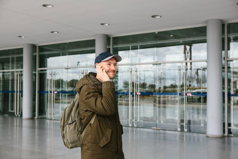 一个年轻男性游人在机场或在购物中心或驻地附近在手机叫出租汽车或谈话或 库存照片