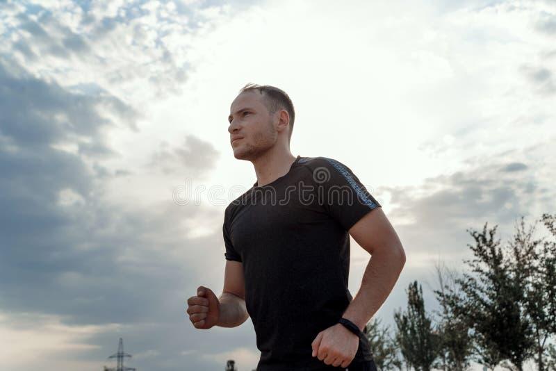 一个年轻白种人人的画象跑在粗糙的地面的黑T恤杉和黑短裤的在日落期间 库存照片
