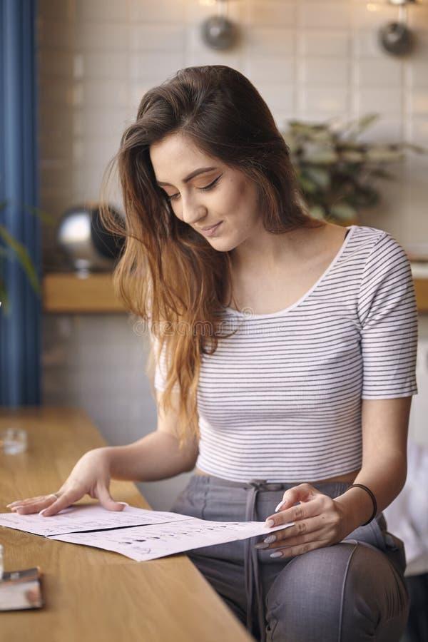 一个年轻白种人女孩在caffee,看菜单坐桌 库存图片