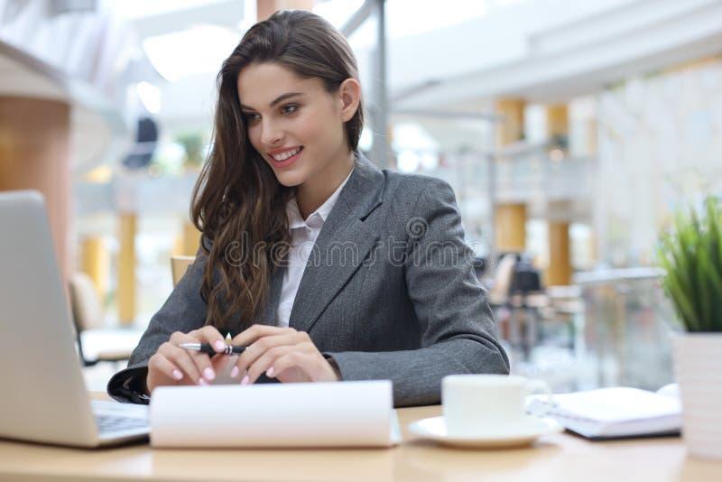一个年轻白肤金发的女商人的画象使用膝上型计算机的在办公室 免版税图库摄影