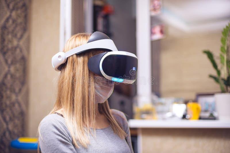 一个年轻白肤金发的白种人病的女孩盖她的面孔并且佩带一个虚拟现实耳机享受在她的虚拟现实 图库摄影