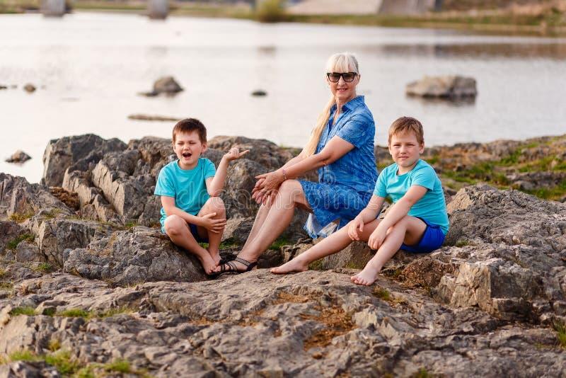 一个年轻祖母和两个孙坐 免版税库存图片