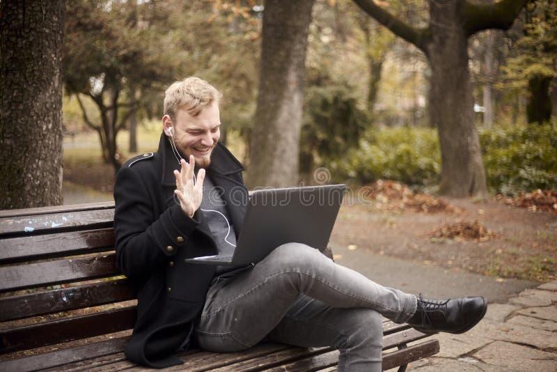 一个年轻笑的人,坐长凳在公园,使用膝上型计算机,谈话在互联网,视频聊天或电话,可能是与 库存照片