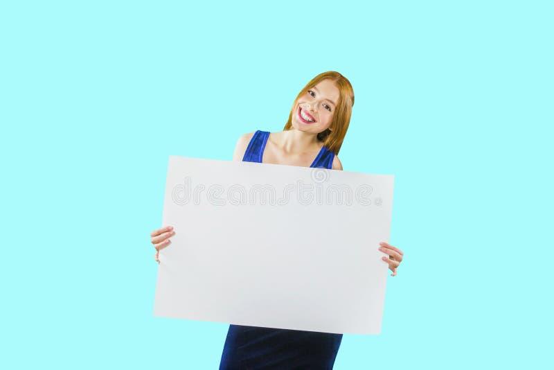 一个年轻红发女孩拿着摆在与微笑的照相机的一张大白色海报或纸在  库存图片