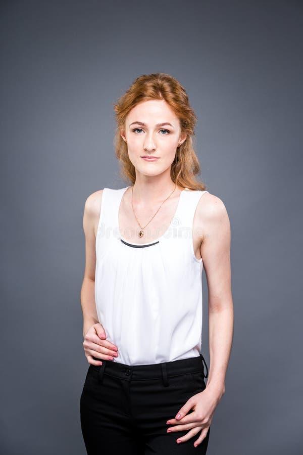 一个年轻红发美丽的女孩的画象在灰色的演播室隔绝了背景 妇女站立与她的被交叉的双臂 免版税库存照片