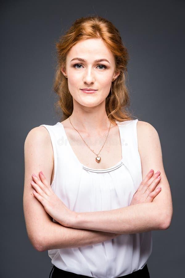 一个年轻红发美丽的女孩的画象在灰色的演播室隔绝了背景 妇女站立与她的被交叉的双臂 库存图片