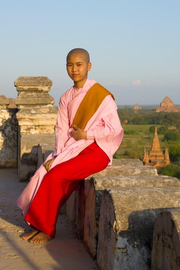 一个年轻缅甸尼姑女孩坐古老佛教寺庙的栏杆 免版税库存图片