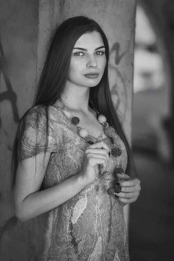 一个年轻美丽的女孩的画象在专栏附近的 库存图片