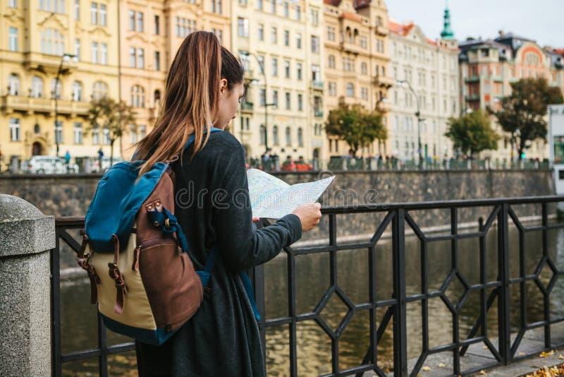 一个年轻美丽的女孩站立并且看地图在有布拉格惊人的老建筑学的伏尔塔瓦河河旁边  库存照片