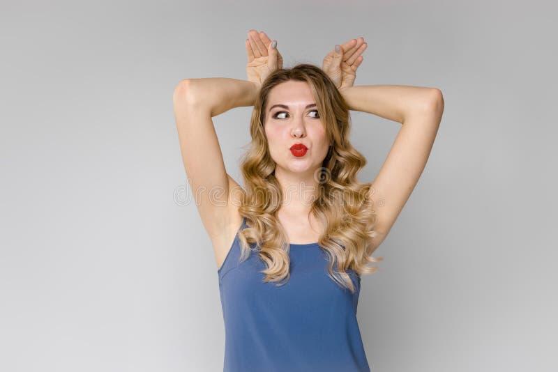 一个年轻美丽的女孩通过把两只手放在她的头上和扭转她的面孔唬弄 一个女孩的滑稽的画象a的 库存照片