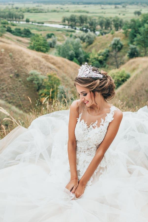一个年轻美丽的微笑的新娘的画象河和领域的一个出色的意见的背景的 库存图片
