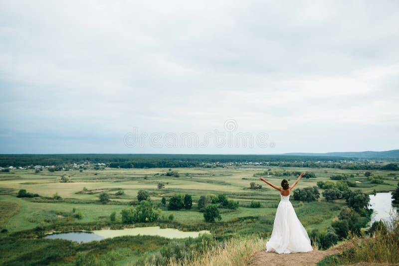 一个年轻美丽的新娘的画象河和领域的一个出色的意见的背景的 婚礼礼服的女孩 图库摄影