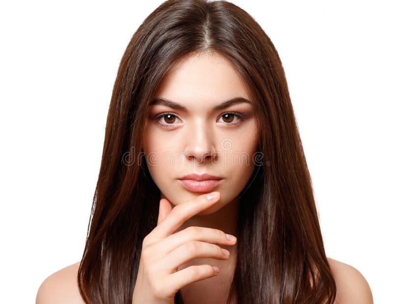 一个年轻美丽的深色的女孩的秀丽画象有棕色在白色背景隔绝的眼睛和平直的长的流动的头发的 库存图片