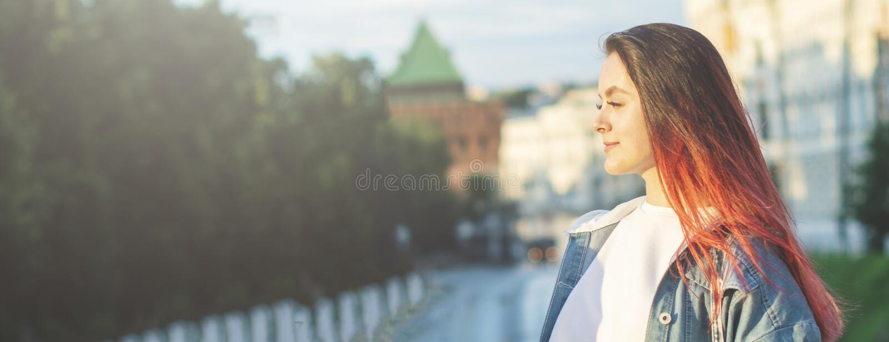 一个年轻美女女学生的画象有a的幸福微笑在街道上在一个夏日 ?? 库存图片