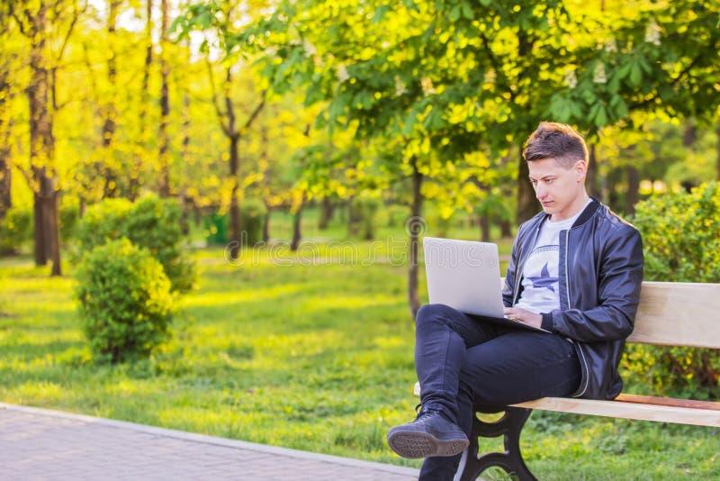 一个年轻英俊的人是坐和工作在有膝上型计算机的公园 人自由职业者工作得外面 免版税库存照片