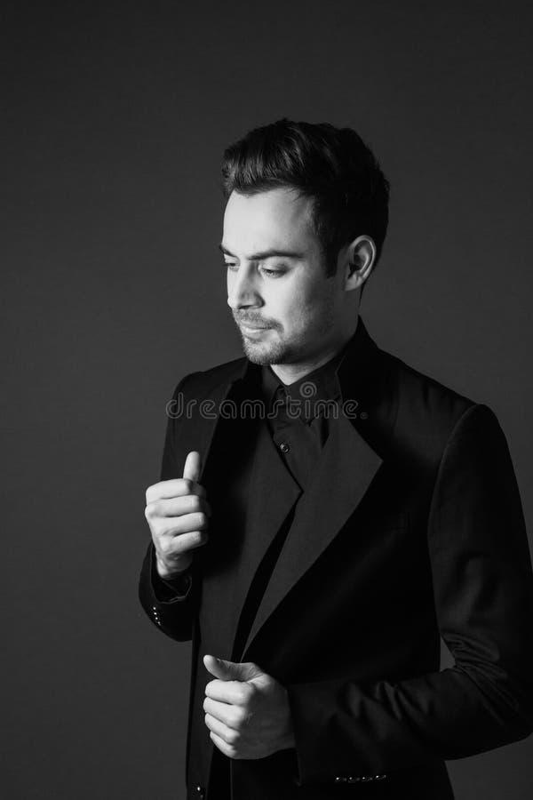 一个年轻英俊的人的黑白画象一衣服,身分和看的在边,在夹克的手 免版税库存照片