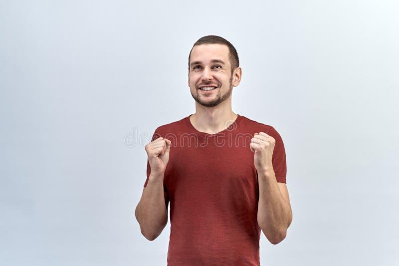 一个年轻英俊的人,红色衬衣的人在他前面举行握紧了入拳头手 库存照片