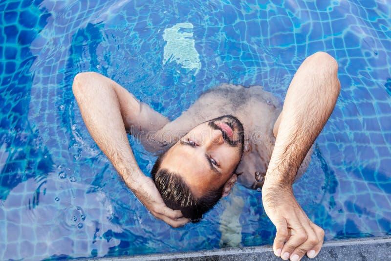 一个年轻英俊的残酷拉丁人的画象一个室外水池的 图库摄影