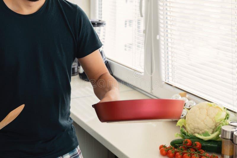 一个年轻英俊的深色的人在厨房里在他的手上站立并且拿着一个煎锅 免版税库存照片