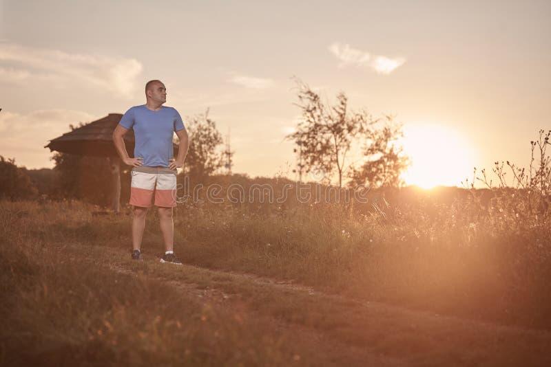 一个年轻超重人, 30-35年,骄傲,摆在站立,金黄橙色日落, 图库摄影
