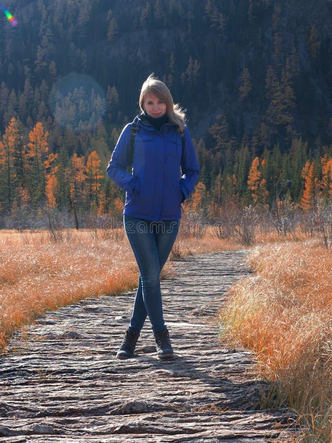 一个年轻运动女孩在水的一条木道路站立在秋天冷淡的季节 库存照片
