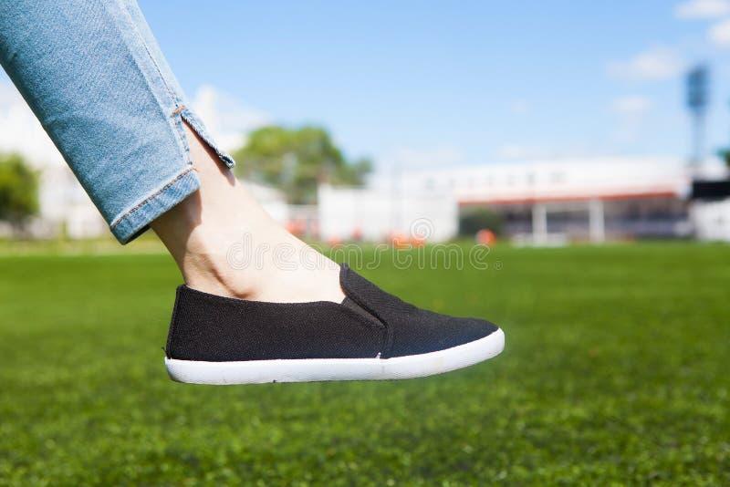 一个年轻运动女孩的腿和橄榄球场的草坪 免版税库存图片