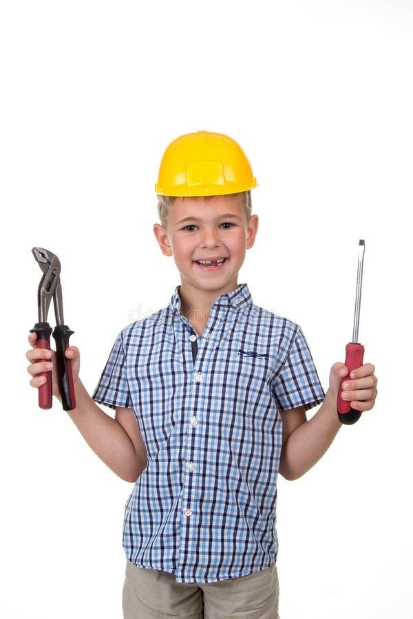一个年轻逗人喜爱的建造者男孩的演播室图片一件蓝色方格的衬衣和黄色盔甲的,拿着大厦仪器 免版税库存照片