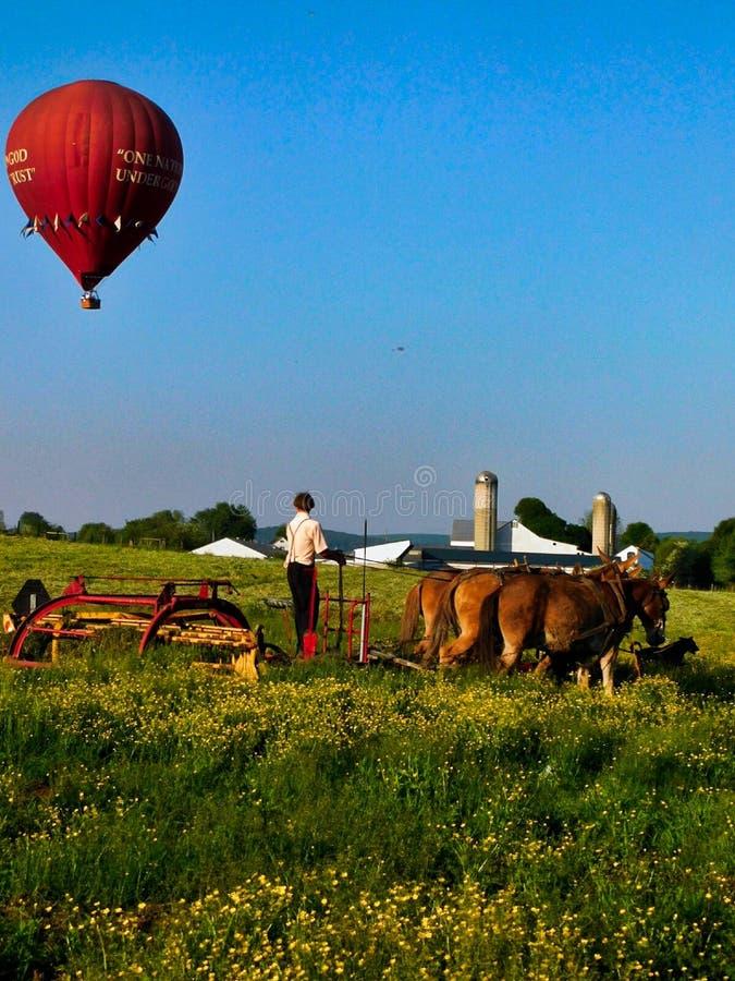 一个年轻门诺派中的严紧派的人剪在领域的草,当一个热空气气球盘旋上面 免版税库存照片