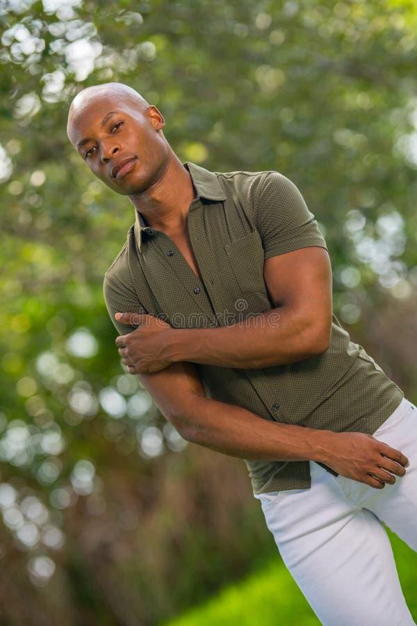 一个年轻非裔美国人的人的画象顽固的家伙姿势的与胳膊横渡了 免版税库存照片