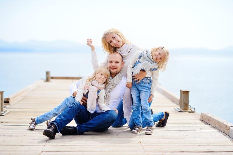 一个年轻,友好的家庭:父亲、母亲和两个女儿坐o 免版税库存图片