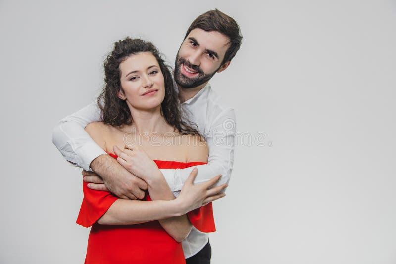 一个年轻,有同情心的人轻轻地拥抱他美丽的妻子 在一件红色礼服打扮的这个女孩期间,白色的一个人 免版税图库摄影