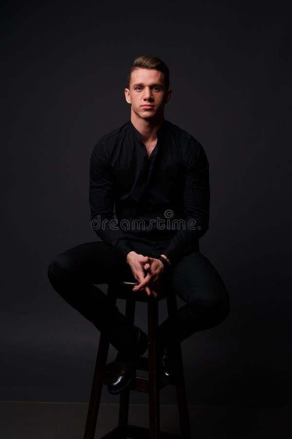 一个年轻,白人坐在一条黑衬衣和黑裤子的一把椅子,反对黑背景和看照相机 事务, m 免版税库存图片