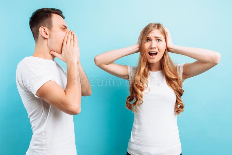 一个年轻,积极的人呼喊在妇女的,妇女用他的手盖她的耳朵,在蓝色背景 免版税库存图片