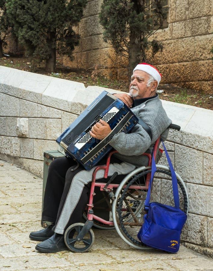 一个年长人在他的手上坐轮椅并且拿着一部手风琴在老城拿撒勒在以色列 免版税库存图片