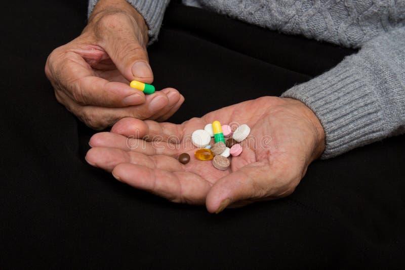 一个年长人在老手上拿着很多色的药片 痛苦的晚年 老人医疗保健  库存照片