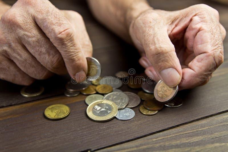 一个年长人拿着硬币 叫化子的手有少量硬币的 贫穷的概念在退休的 免版税库存照片