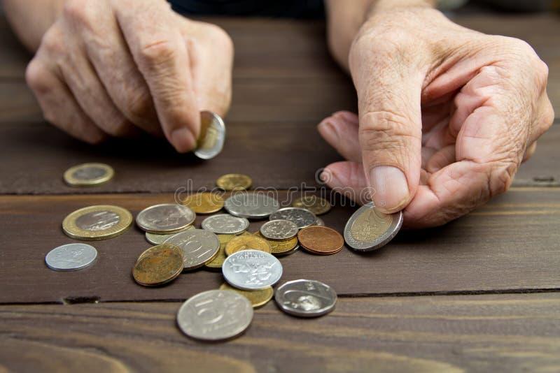 一个年长人拿着硬币 叫化子的手有少量硬币的 贫穷的概念 免版税库存照片