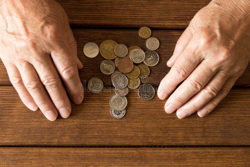 一个年长人的手有各种各样的硬币的在一张木桌上 Th 库存照片