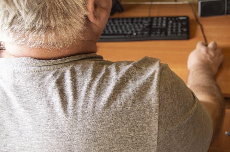 一个年长灰发的人使用一只计算机老鼠,为残疾在家工作,训练领抚恤金者在个人计算机工作,一个看法从 免版税库存照片