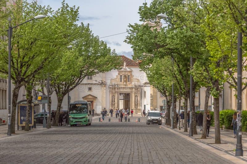 一个广场的看法,有科英布拉大学的铁门的,与石工的经典建筑结构,与人,树和 库存照片