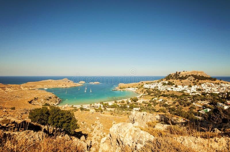 一个广角垂直的风景视图和射击从一座山到一个小的村庄Lindos在罗得岛,希腊和那里是帆船 免版税库存图片
